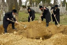 <p>Rabbis from England and the United States bury the remains of dozens of Jews in a cemetery in Iasi, 410 km (251 miles) north of Bucharest, April 4, 2011. REUTERS/Bogdan Cristel</p>