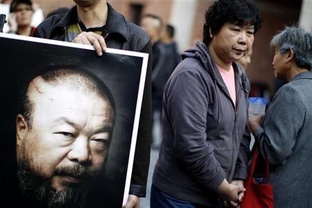 A supporter of prominent Chinese artist Ai Weiwei holds a picture of him at Weiwei's art studio to protest the demolition of the place by the government in Shanghai November 7, 2010. REUTERS/Carlos Barria