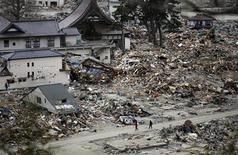 <p>Люди идут мимо разрушенных зданий в Исиномаки на севере Японии, 4 апреля 2011 года. В статье приводятся некоторые цифры, позволяющие судить о масштабах последствий землетрясения и цунами в Японии, произошедших 11 марта. REUTERS/Carlos Barria</p>