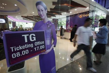 Passengers walk past a ticketing office at the Thai Airways International headquarters in Bangkok August 2, 2010. REUTERS/Chaiwat Subprasom