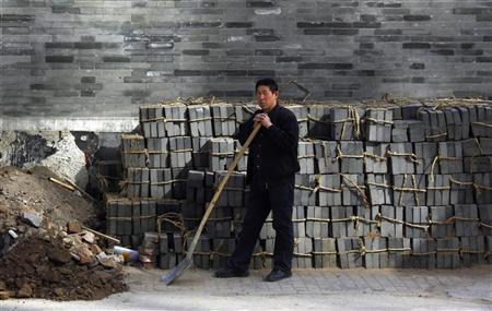 A worker rests on his shovel in front of a residential home under renovation located in a ''hutong'' or small alley, in central Beijing March 25, 2011. REUTERS/David Gray