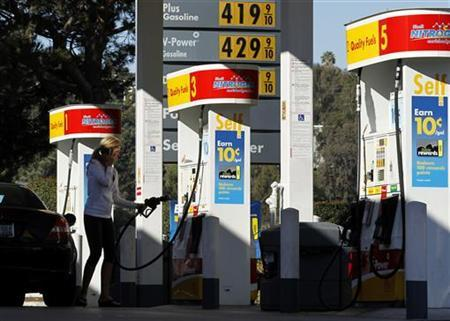 A woman uses her mobile phone at a petrol kiosk in Dal Mar, California March 1, 2011. REUTERS/Mike Blake