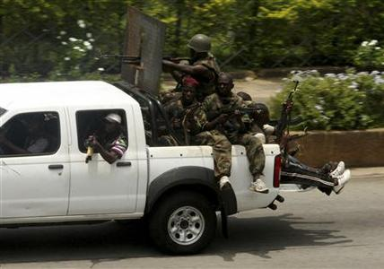 Pro-Gbagbo militia men ride in a pick-up truck in Abidjan April 6, 2011. REUTERS/Luc Gnago