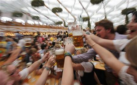People wearing traditional Bavarian clothes toast with beer during the opening day of the 177th Oktoberfest in Munich September 18, 2010. REUTERS/Leonhard Foeger