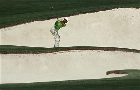 Tiger Woods hits from a sand trap on the eighth fairway during first round play in 2011 Masters golf tournament at the Augusta National Golf Club in Augusta, Georgia, April 7, 2011. REUTERS/Brian Snyder