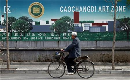 A man rides a bicycle past a billboard located near the entrance to the studio owned by detained activist Ai Weiwei in Beijing April 8, 2011. REUTERS/David Gray
