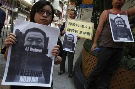 Pro-democracy protesters carry portraits of detained Chinese artist Ai Weiwei urging for his release before walking to a China's liaision office in Hong Kong April 10, 2011. Chinese characters on a placard reads ''Release pro-democracy protesters. To build a democratic China''. REUTERS/Bobby Yip