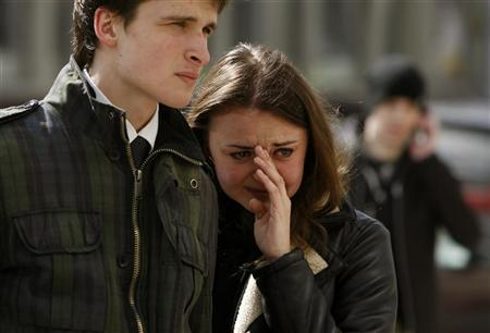 A woman pays cries near the entrance to the Oktyabrskaya metro station in Minsk April 12, 2011. REUTERS/Vladimir Nikolsky
