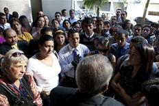 <p>Bank employees and customers listen to a bank official speak outside a branch of Banco Canarias in Caracas November 30, 2009. REUTERS/Carlos Garcia Rawlins</p>