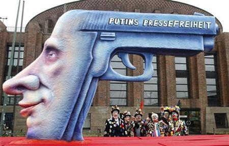 Revellers stand next to a carnival float with a large papier-mache figure of a gun as Russia's Prime Minister Vladimir Putin, with 'freedom of press' written on it, is pictured during the traditional Rose Monday carnival parade in Duesseldorf February 23, 2009. REUTERS/Ina Fassbender