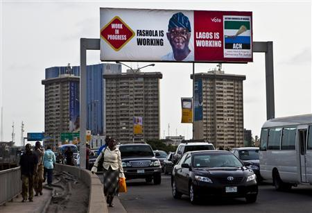 Traffic passes under an electoral campaign poster for Lagos' governor Babatunde Raji Fashola in Ikoyi district April 11, 2011. REUTERS/Joseph Penney