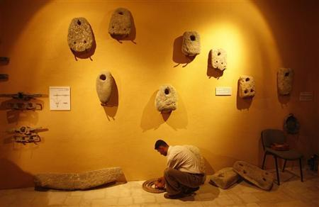 A Palestinian works in the privately owned and operated Museum of Archeology in Gazaon July 30, 2008. REUTERS/Ibraheem Abu Mustafa