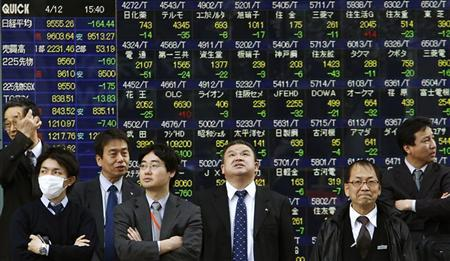 Businessmen wait to cross a street in Tokyo, April 12, 2011. REUTERS/Yuriko Nakao