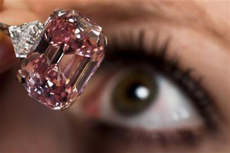 An employee poses with a 24.78 carat Fancy Intense Pink diamond at Sotheby's in Geneva November 10, 2010. REUTERS/Valentin Flauraud