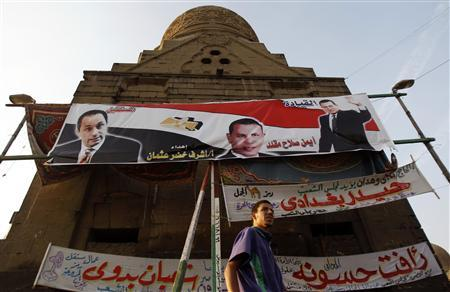 A man walks past electoral banners for Egypt's ruling National Democratic Party (NDP) showing Egypt's President and head of the ruling NDP Hosni Mubarak (R), his son and NDP deputy head Gamal Mubarak (L) and NDP politician and candidate Ayman Salah Mekled (C) in Cairo in this November 22, 2010 file photo. The poster reads: ''The leadership and the future''. REUTERS/Amr Abdallah Dalsh/Files