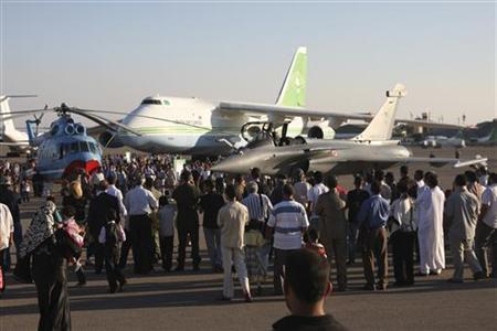 Visitors look at a French Rafale warplane during the Lavex 2009 Airshow at the Mitiga air base near Tripoli in this undated photograph. Almost every modern conflict from the Spanish Civil War to Kosovo has served as a test of air power. But the Libyan operation to enforce UN resolution 1973 coincides with a new arms race --a surge of demand in the $60 billion a year global fighter market and the arrival of a new generation of equipment in the air and at sea. For the countries and companies behind those planes and weapons, there's no better sales tool than real combat. For air forces facing cuts, it is a strike for the value of air power itself. REUTERS/Jaap Dijkstra/www.scramble.nl