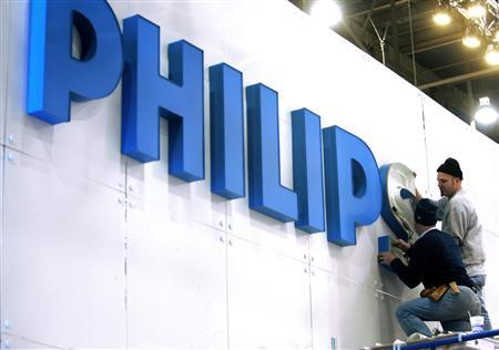 Workers put up a sign at the Philips Electronics booth before the Consumer Electronics Show (CES) at the Las Vegas Convention Center in this January 3, 2008 file photo. Philips is hiving off its once leading television business, the first step by new chief executive Frans van Houten to boost flagging profit at Europe's biggest consumer electronics maker. Philips is moving its loss-making TV business to a 30/70 joint venture with Hong-Kong based monitor maker TPV and has the option to sell out. The Dutch group has struggled to compete against players like Samsung and LG Electronics. Van Houten, a restructuring expert who took over as CEO this month, said on April 18, 2011 he is assessing the profitability of Philips' 400 or so business areas, a hint that further divestments could be on the cards. REUTERS/Las Vegas Sun/Steve Marcus/Files (