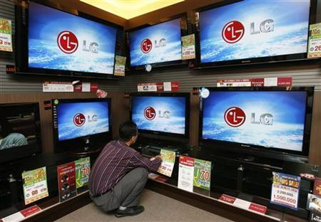 An employee of LG Electronics' home appliances store checks its LCD televisions displayed for customers at a store in Seoul April 16, 2008. REUTERS/Jo Yong-Hak