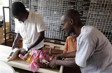 Kenyan nurses weigh a child before she is given an injection as part of a malaria vaccine trial at a clinic in the Kenya coastal town of Kilifi, November 23, 2010. REUTERS/Joseph Okanga