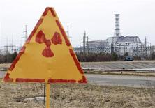 """<p>Саркофаг над четвертым реактором Чернобыльской атомной станции на фоне знака радиации 4 апреля 2011 года. Украина собрала 550 миллионов евро ($780 миллионов) на строительство нового саркофага над разрушенным 25 лет назад четвертым реактором Чернобыльской атомной станции и другие """"чернобыльские"""" проекты, сообщили после международной конференции стран-доноров президент Украины Виктор Янукович и премьер-министр Франции Франсуа Вийон. REUTERS/Gleb Garanich</p>"""