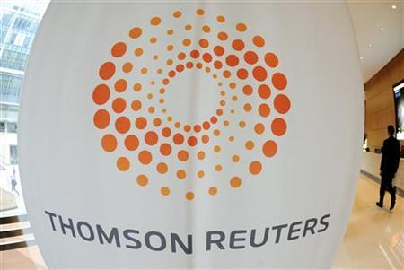 A man walks near a Thomson Reuters logo at the Thomson Reuters building in Canary Wharf in east London May 7, 2009.