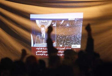Demonstrators gesture as they listen to Egyptian President Hosni Mubarak's televised speech screened in Tahrir Square in Cairo February 10, 2011. REUTERS/Asmaa Waguih