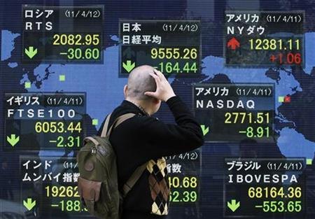 A man looks at the closing price of Japan's Nikkei share average (top C) displayed along with major indices outside a brokerage in Tokyo April 12, 2011. REUTERS/Yuriko Nakao