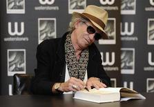 <p>O músico Keith Richards assina cópia de sua autobiografia em Londres, em novembro de 2010. Livros contando a vida dos astros de rock, como o de Richards, estão ajudando as vendas do mercado editorial. 03/11/2010 REUTERS/Paul Hackett</p>