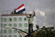 <p>Оппозиционер держит флаг Йемена в городе Таиз 8 апреля 2011 года. Йеменская оппозиция согласилась войти в переходное правительство, создание которого предусматривает мирный план Совета сотрудничества арабских стран Персидского залива, сообщил Рейтер источник в оппозиционных кругах. REUTERS/Khaled Abdullah</p>