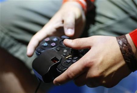 A visitor plays with a 'Playstation' at an exhibition stand at the Gamescom 2009 fair in Cologne in this August 22, 2009 file photo. REUTERS/Ina FAssbender