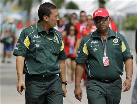 Lotus Formula One team principal Tony Fernandes (R) arrives for the third practice session of the Malaysian F1 Grand Prix at Sepang circuit outside Kuala Lumpur April 9, 2011. REUTERS/Tim Chong