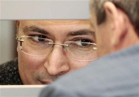 Jailed Russian former oil tycoon Mikhail Khodorkovsky (L) talks to a lawyer from the defendant's cage during a session of the Russian Supreme court in Moscow April 15, 2011. REUTERS/Alexander Natruskin