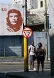 <p>Foto de archivo de unas personas en una calle de La Habana, feb 8 2011. En Cuba, donde la música de la banda de rock británica The Beatles estuvo prohibida por años, un club nocturno propiedad del Gobierno comunista está reivindicando al mítico grupo y borrando antiguos tabúes ideológicos, dijeron directivos y clientes. REUTERS/Enrique De La Osa</p>
