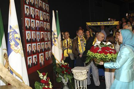 National Council of Resistance of Iran (NCR) leader Maryam Rajavi (R) lays flowers for those who were killed in Camp Ashraf, at a meeting in Marly-le-Roi, near Paris, April 27, 2011 in this photo released to media by the National Council of Resistance of Iran. Rajavi was in France to attend the event organised by the National Council of Resistance, the Mujahideen's political wing, to demand international protection for Camp Ashraf, scene of this month's deadly clash. REUTERS/National Council of Resistance of Iran/Handout