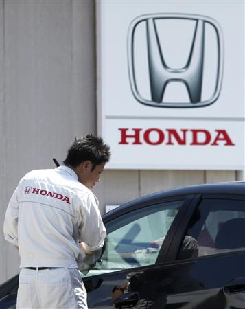 An employee wipes a window at a Honda dealer in Kawasaki, south of Tokyo April 28, 2011. Honda Motor Co reported a 52 percent fall in quarterly operating profit and refrained from providing an outlook for the new year as it struggles to measure the speed of its recovery after last month's massive earthquake in Japan. REUTERS/Yuriko Nakao