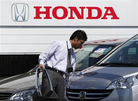 An employee of a Honda dealer prepares to open for business in Kawasaki, south of Tokyo April 28, 2011. Honda Motor Co reported a 52 percent fall in quarterly operating profit and refrained from providing an outlook for the new year as it struggles to measure the speed of its recovery after last month's massive earthquake in Japan. REUTERS/Yuriko Nakao