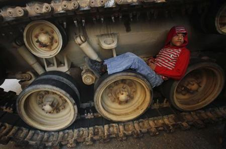 A boy sits inside the tracks of an army tank in Tahrir Square, Cairo, February 18, 2011. REUTERS/Suhaib Salem