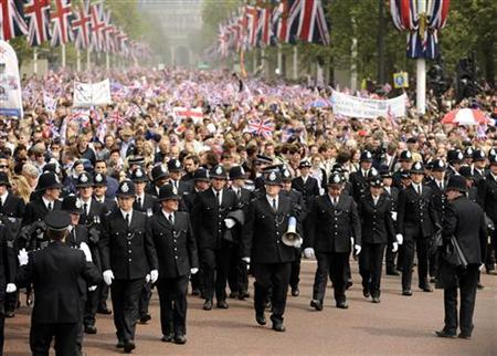Police officers escort Royal watchers along The Mall towards Buckingham Palace after the wedding of the Procession of Britain's Catherine, Duchess of Cambridge and Prince William after their wedding in Westminster Abbey, in central London April 29, 2011. REUTERS/Dylan Martinez