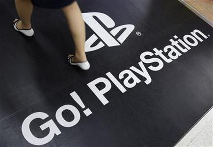 A woman walks on a floor advertisement for Sony Corp's PlayStation 3 game console at an electronic store in Tokyo April 27, 2011. REUTERS/Yuriko Nakao