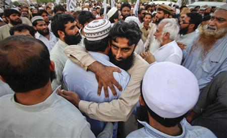 Supporters of the banned Islamic organization Jamaat-ud-Dawa embrace each other after taking part in a funeral prayer for al Qaeda leader Osama bin Laden in Karachi, May 3, 2011. REUTERS/Athar Hussain
