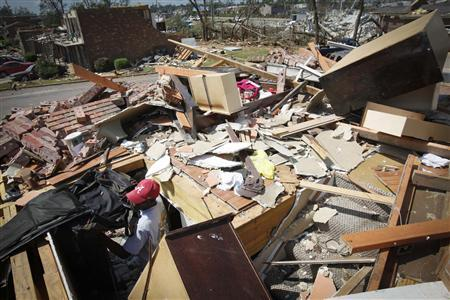 Sydney Maxwell looks for his belongings in his apartment destroyed in April 27's deadly tornados in Tuscaloosa, Alabama May 2, 2011. REUTERS/Lee Celano
