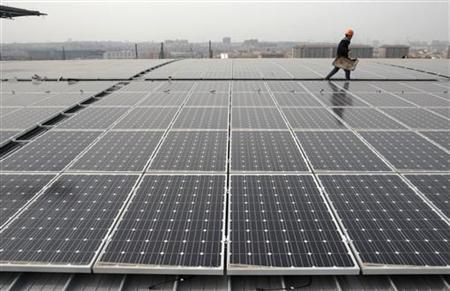 A worker walks past sets of solar panels on the rooftop of the Nanjing South Railway Station which is under construction in Nanjing, Jiangsu province March 23, 2011. REUTERS/Sean Yong/Files