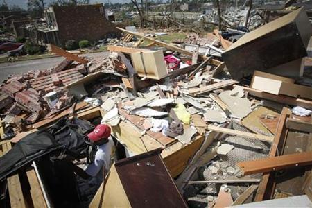 Sydney Maxwell looks for his belongings in his apartment destroyed in April 27's deadl tornados in Tuscaloosa, Alabama May 2, 2011. REUTERS/Lee Celano