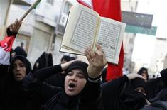 <p>A Bahraini woman holds a Koran over her head as she shouts anti-government slogans during a protest in the mainly Shi'ite village of Diraz, west of Manama, March 25, 2011. REUTERS/Hamad I Mohammed</p>