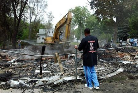 In this file photot Rodney Dyson watches as a bulldozer buries his parents still smoldering burned house June 18, 2003 in Benton Harbor, Michigan. REUTERS/Rebecca Cook