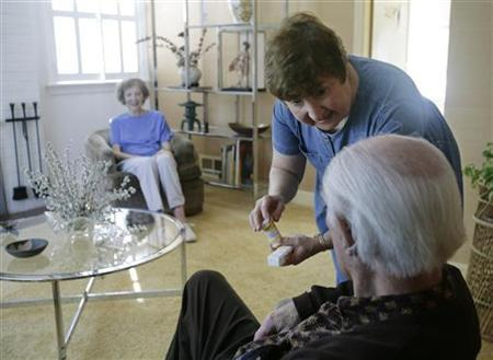 Volunteer parish nurse Joanie Friend (top) of the Bradley Hills Presbyterian Church discusses the medication of elderly patient Hazel Sears (L) with her husband Marvin and asks for his assistance in making sure his wife takes her pills, at the Sears' home in Bethesda, Maryland, September 21, 2007. REUTERS/Jim Bourg