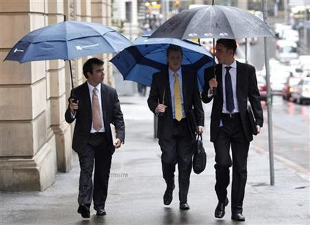Office workers hold umbrellas as they walk in central Sydney February 5, 2010. REUTERS/Daniel Munoz