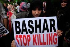 """<p>Девушка держит в руках плакат """"Башар, прекрати убийства"""" на демонстрации у сирийского посольства в Лондоне 7 мая 2011 года. Танки войск правительства обстреляли жилые районы в двух сирийских городах в среду, в результате чего как минимум 19 человек погибли, сообщили правозащитники. REUTERS/Andrew Winning</p>"""
