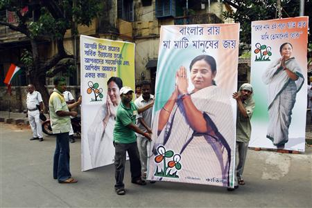 Supporters of the Trinamool Congress party hold election billboards featuring portraits of party leader Mamata Banerjee in Kolkata, May 13, 2011. REUTERS/Rupak De Chowdhuri
