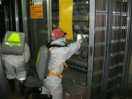 Workers wearing protective suits check the status of the water level indicator at the fuel area inside Tokyo Electric Power (TEPCO) Co.'s crippled Fukushima Daiichi Nuclear Power Plant No.1 reactor in Fukushima Prefecture May 10, 2011 in this handout photo released by TEPCO on May 12, 2011. REUTERS/Tokyo Electric Power Co/Handout